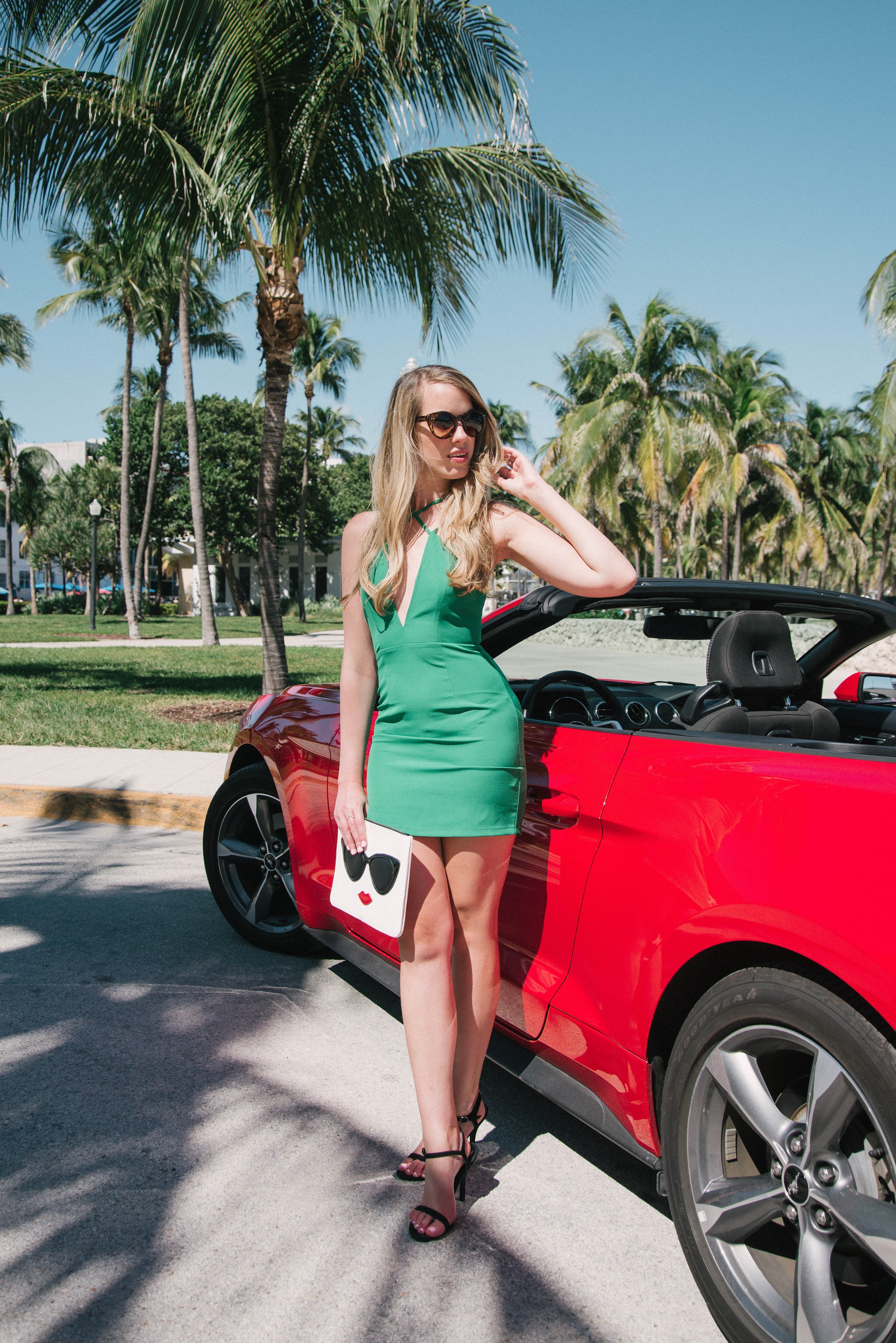 Miami standing near a red ford mustang